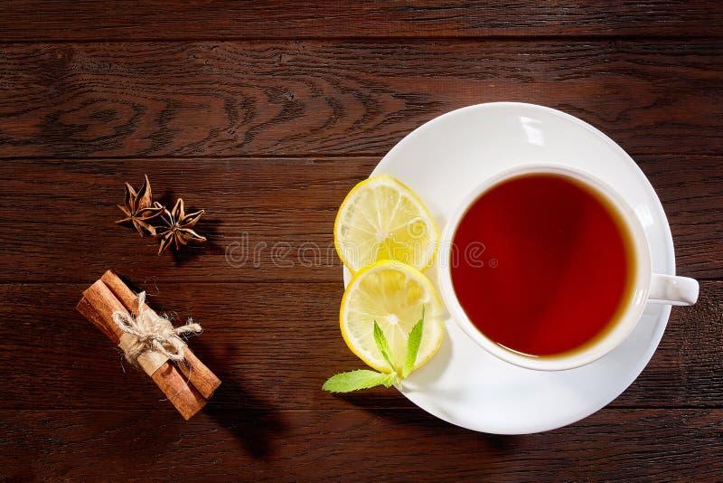 Tasse blanche de thé avec les bâtons de cannelle, le citron, les feuilles en bon état et le tamis de thé sur la table rustique en photographie stock libre de droits
