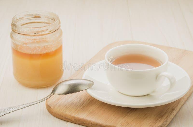 Tasse blanche de thé avec un pot ouvert de miel/de tasse blanche de thé avec photos libres de droits
