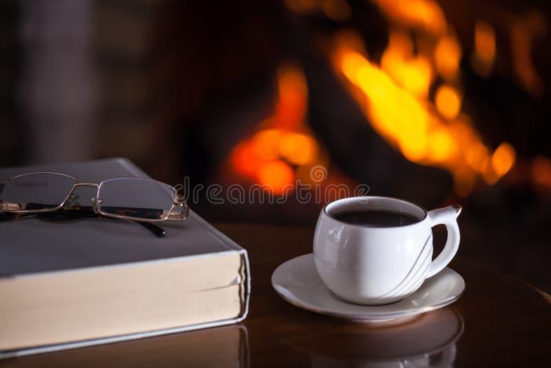 Tasse blanche de thé ou café, verres et vieux livre près de cheminée photographie stock libre de droits