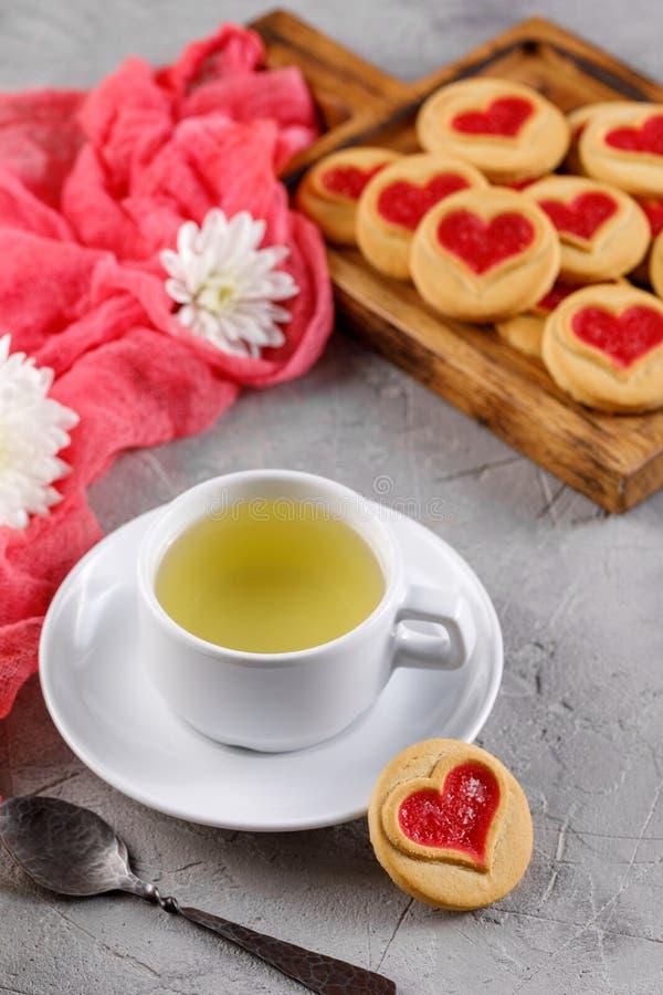 Tasse blanche de thé vert et de biscuits avec des coeurs sur un fond gris La belle vie immobile, l'humeur de la Saint-Valentin image stock