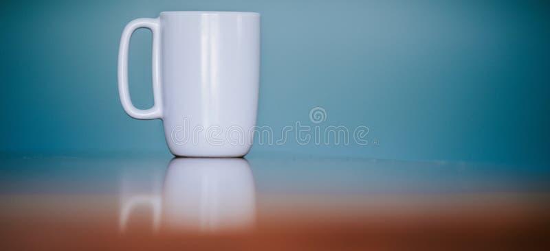 Tasse blanche sur une surface se reflétante avec un fond bleu et espace pour le texte photographie stock