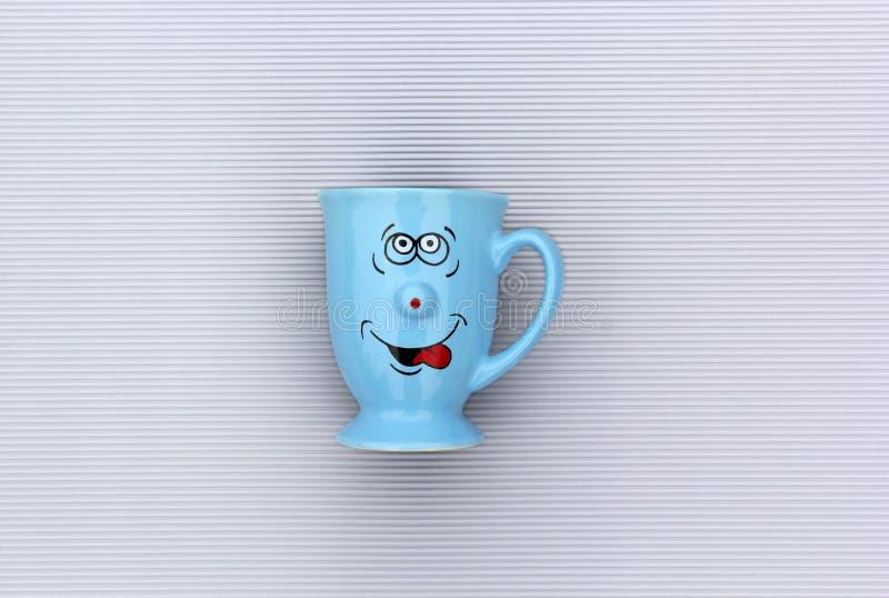 Tasse bleue de café avec le visage heureux de sourire sur le fond gris Bonjour, concept créatif de carte de voeux image stock