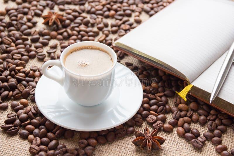 Tasse, carnet et stylo de café blanc sur le fond des grains de café photos stock