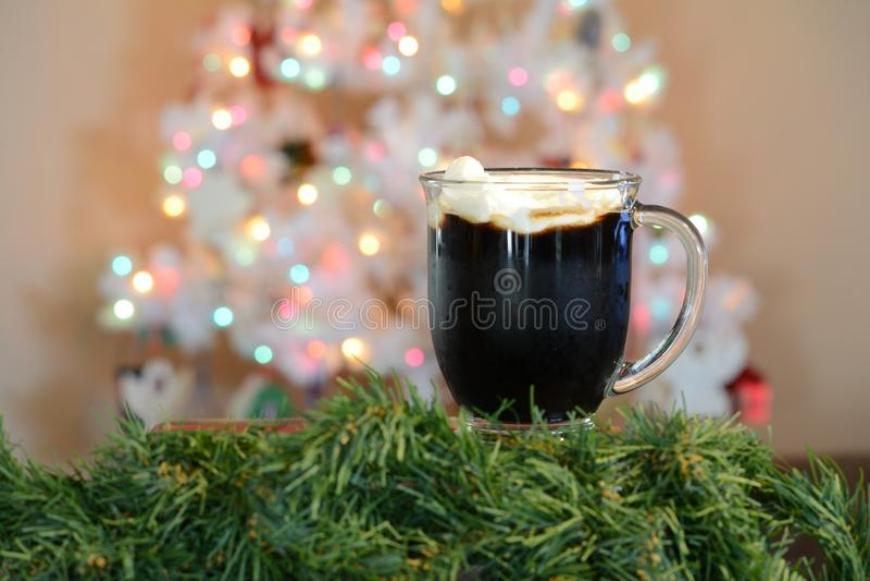 Tasse chaude de cacao posée devant l'arbre de Noël blanc avec les lumières colorées photo libre de droits