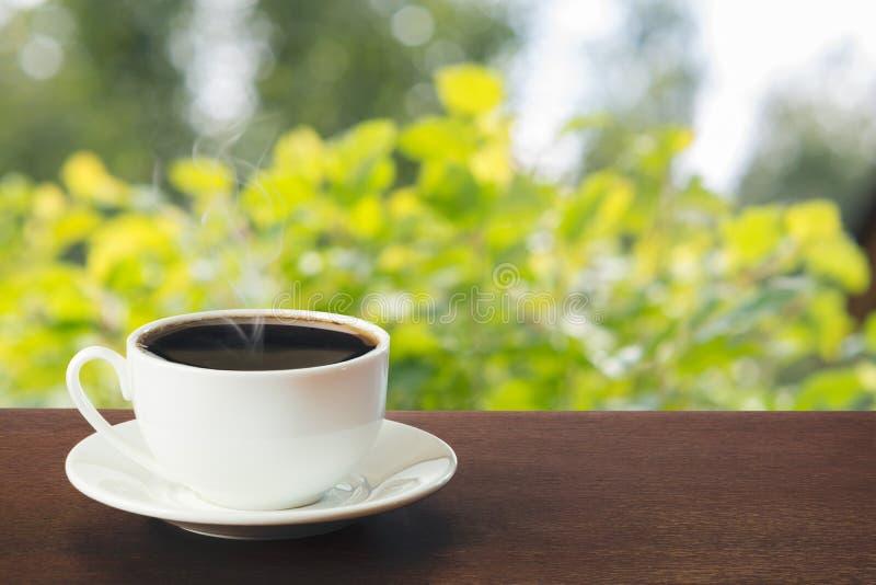 Tasse chaude de café noir dans un jour ensoleillé sur le dessus de table Été outdoors image stock