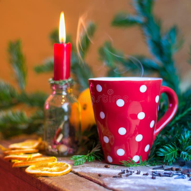 Tasse chaude de cuisson à la vapeur hivernale de thé avec la bougie et les oranges photo stock