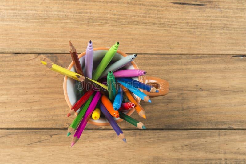 Tasse complètement de marqueurs et de crayons colorés photos stock