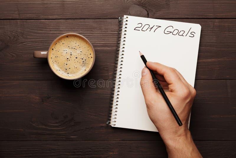 Tasse d'écriture de main de café et de mâle dans des buts de carnet pour 2017 Planification et motivation pour le concept de nouv photos libres de droits