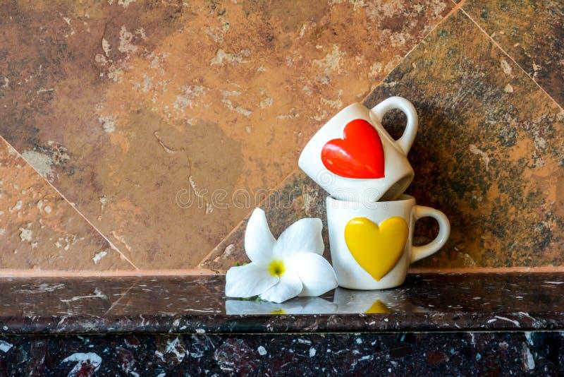 Tasse d'amour avec la fleur photo stock