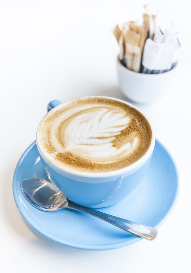 Tasse d'art de latte sur un café de cappuccino dans la tasse bleue photos libres de droits