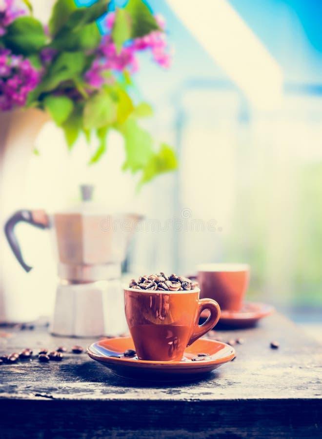 Tasse d'expresso complètement de grains de café sur la table de cuisine avec le pot de café sur le fond de la terrasse photographie stock