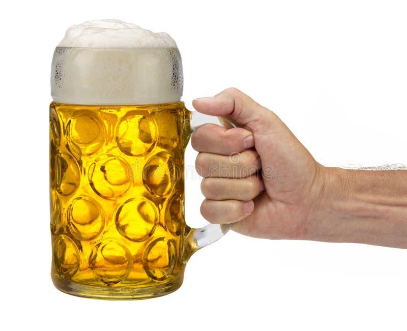 Tasse d'isolement de bière se tenant à disposition chez Oktoberfest en Bavière photos stock