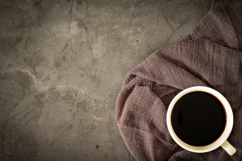 Tasse d'un café noir sur la serviette, vieux plancher de ciment avec la lumière de matin L'espace de copie de vue sup?rieure photos libres de droits