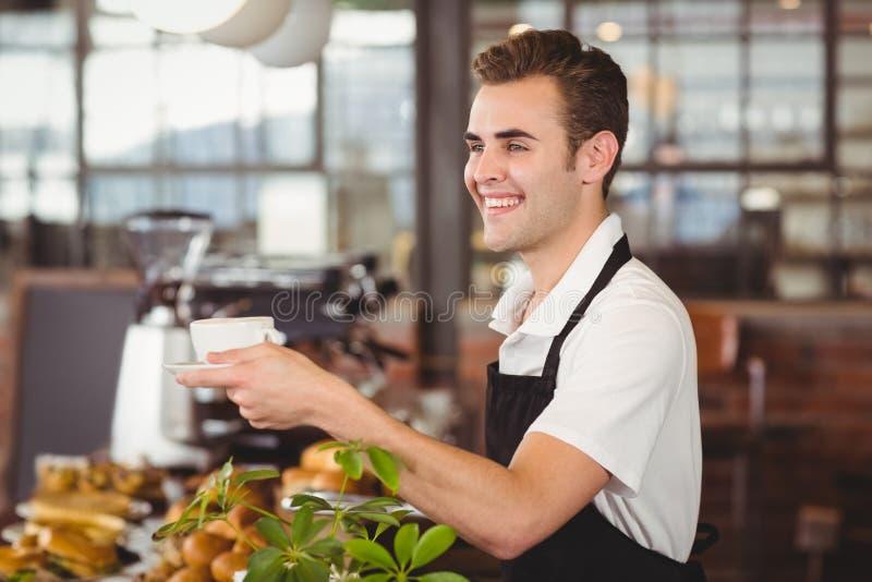 Tasse de barman de café de offre de sourire photographie stock libre de droits