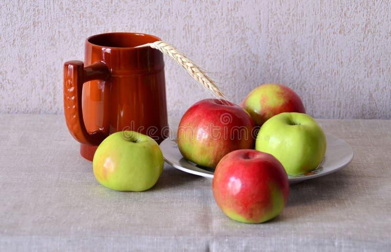 Tasse de bière avec des pommes d'un plat photographie stock libre de droits