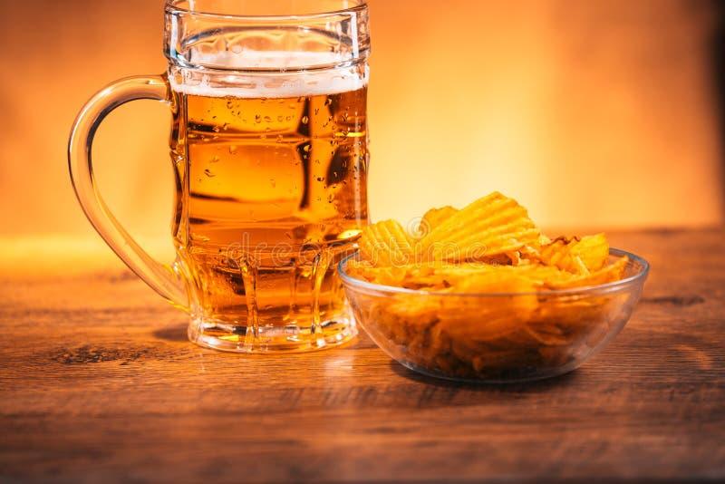 Tasse de bière blonde avec un bol de pommes chips sur une table en bois photo libre de droits