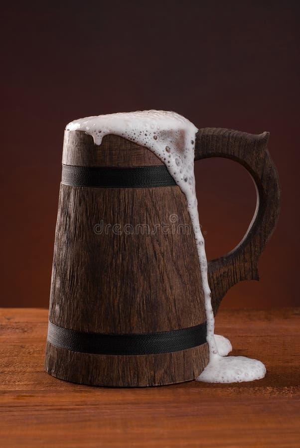 Tasse de bière en bois avec de la mousse sur un fond rouge foncé images libres de droits