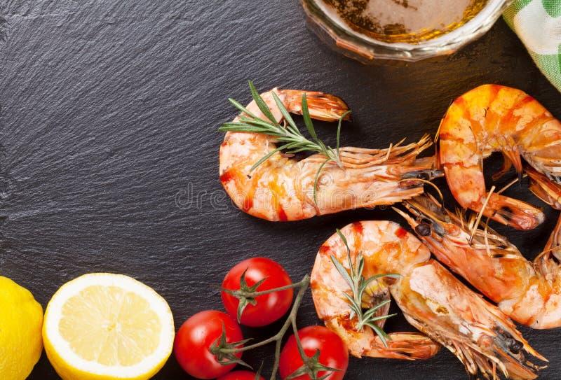 Tasse de bière et crevettes grillées du plat en pierre photographie stock libre de droits