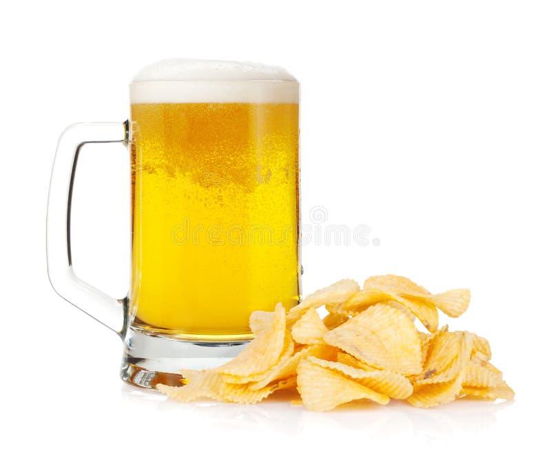 Tasse de bière et pile des pommes chips photographie stock