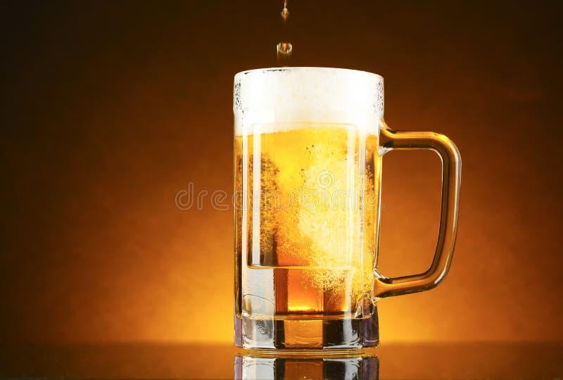 Tasse de bière sur un jaune photos libres de droits