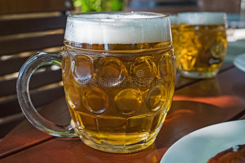Tasse de bière traditionnelle avec la bière blonde blonde dans un caffee de rue image libre de droits