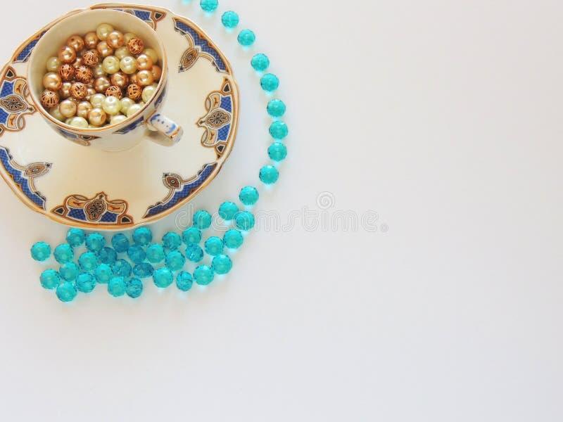 Tasse de bleu de vintage et de thé d'or avec les perles et les cristaux d'or d'imagination photographie stock
