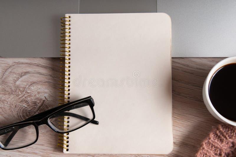 Tasse de bloc-notes, d'ordinateur portable et de café sur la table en bois photographie stock libre de droits