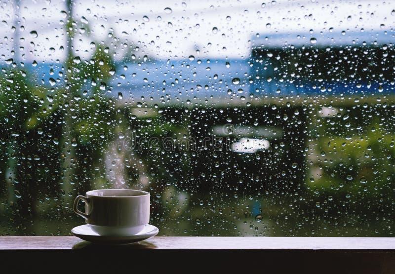Tasse de boisson chaude sur la table en bois dans le jour pluvieux image libre de droits