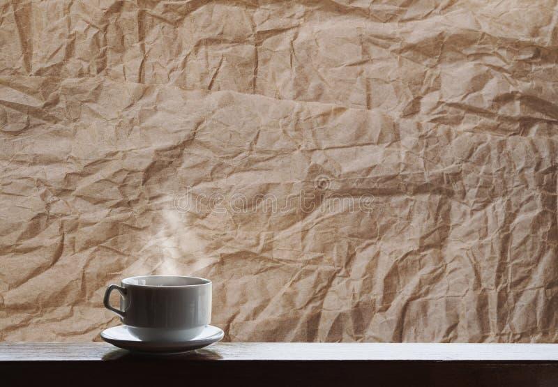 Tasse de boissons chaudes avec la vapeur sur la table en bois, fond chiffonné de texture de papier brun images libres de droits