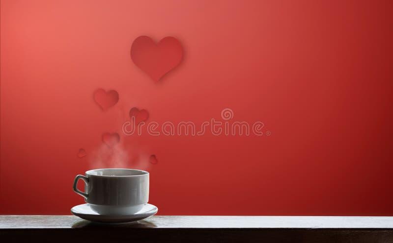 Tasse de boissons chaudes avec le courant, sur le fond rouge avec flotter les coeurs rouges photos libres de droits