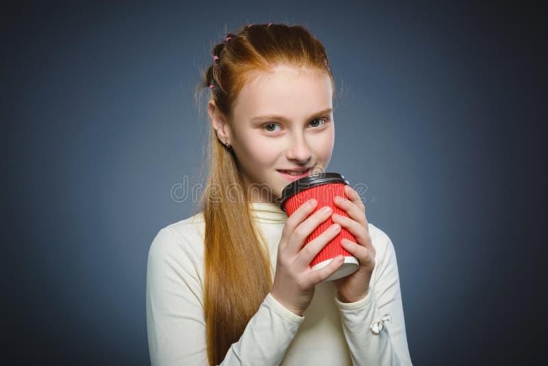 Tasse de boissons d'adolescente de café rouge d'isolement sur le fond gris images stock
