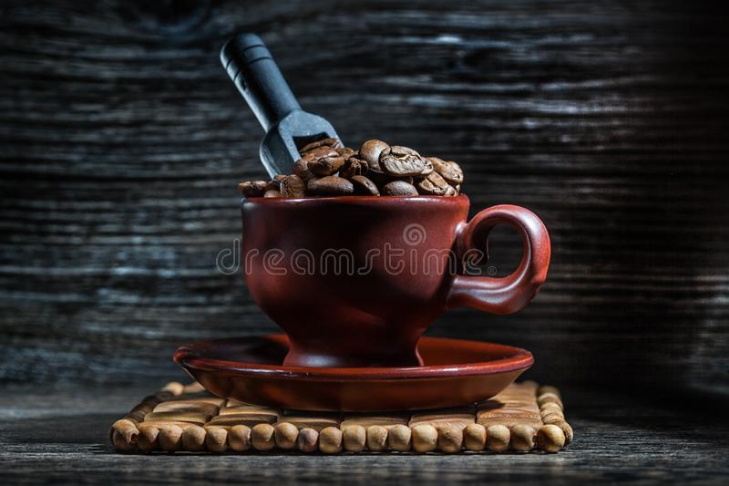 Tasse de Brown avec les grains de café et le petit scoop noir photos libres de droits