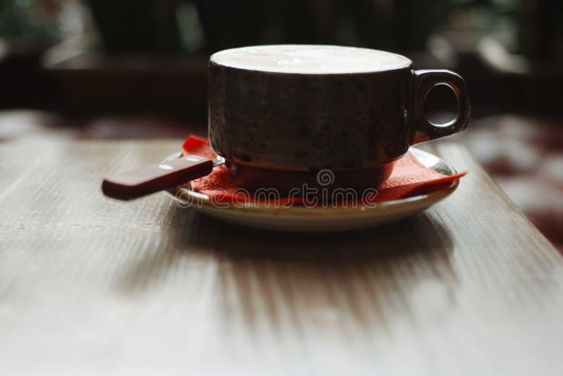 Tasse de Brown de café chaud sur la table en café éclairé à contre-jour - ton de couleur foncée de cru avec des ombres  image stock