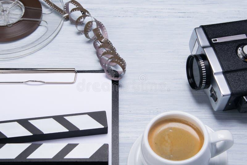 Tasse de café à côté d'une caméra vidéo et d'un film, il y a un endroit pour une inscription, sur un comprimé blanc images stock