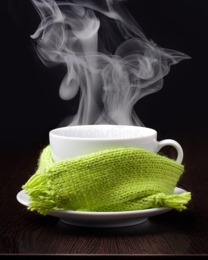 Tasse de café avec de la fumée dans l'écharpe verte photographie stock libre de droits