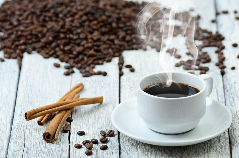 Tasse de café avec de la fumée et des grains de café autour photographie stock libre de droits