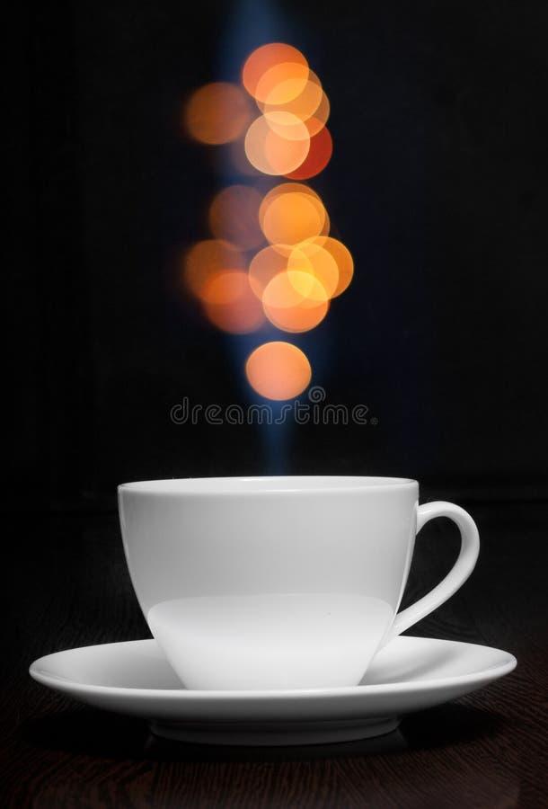 Tasse de café avec de la fumée et le bokeh abstrait photo stock