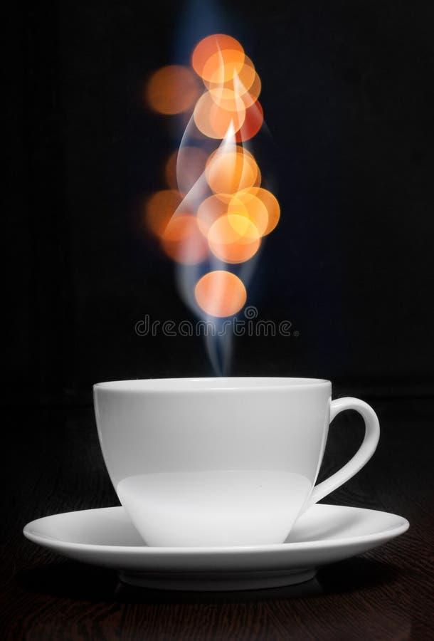 Tasse de café avec de la fumée et le bokeh abstrait photos stock