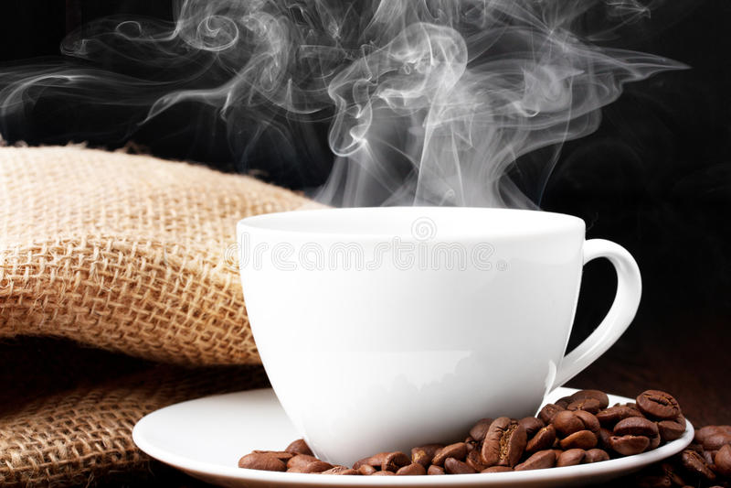 Tasse de café avec de la fumée et le grain image stock