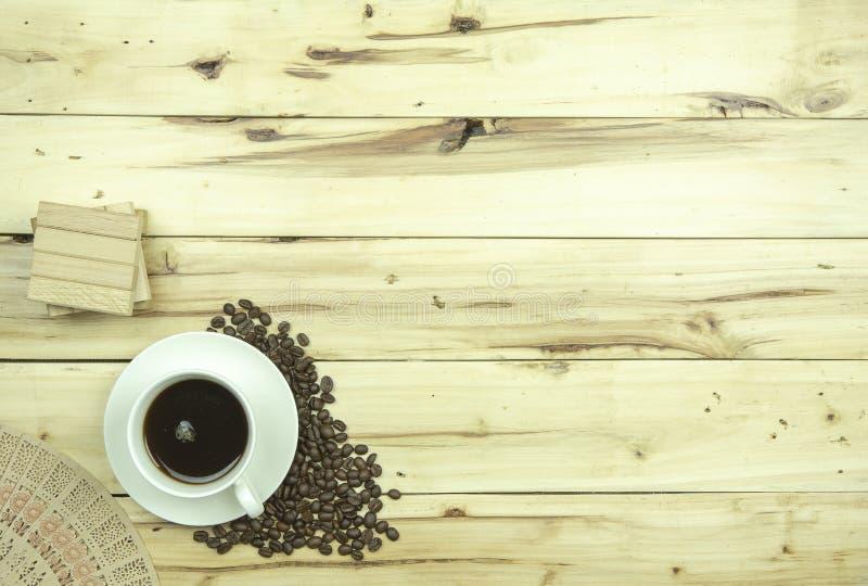 Tasse de café avec des grains de café sur le fond en bois photos stock
