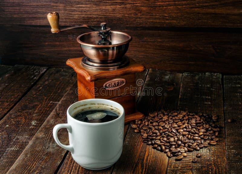 Tasse de café avec des haricots de moulin et de caffee à café sur le fond en bois foncé photo libre de droits