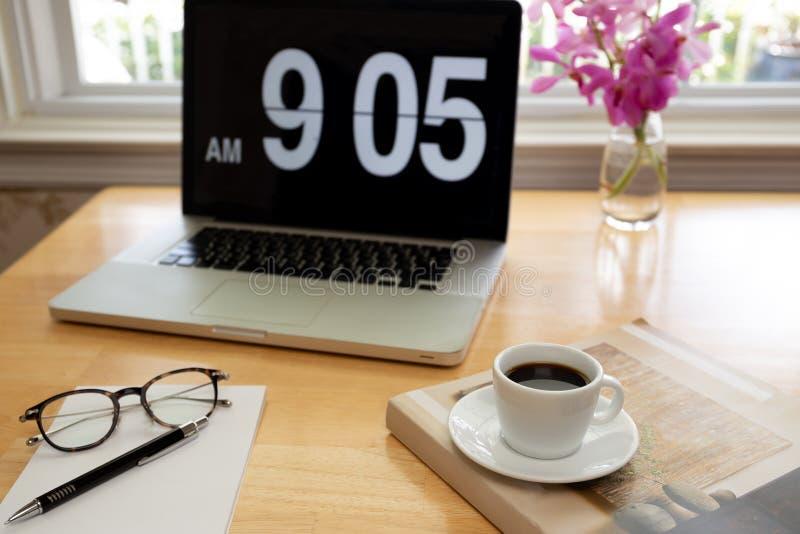 Tasse de café avec des verres et de stylo sur le bureau en bois avec l'ordinateur portable et la fleur image libre de droits