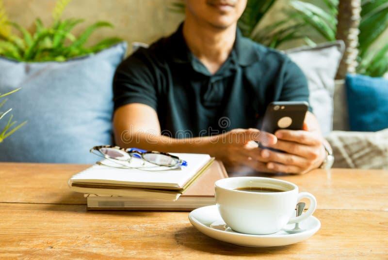 Tasse de café avec l'homme utilisant le téléphone portable et le livre sur la table image stock