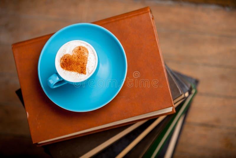 Tasse de café avec de la crème de forme de coeur sur des livres photographie stock libre de droits