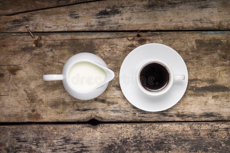 Tasse de café avec la cruche de lait sur le fond en bois. Vue supérieure photos stock