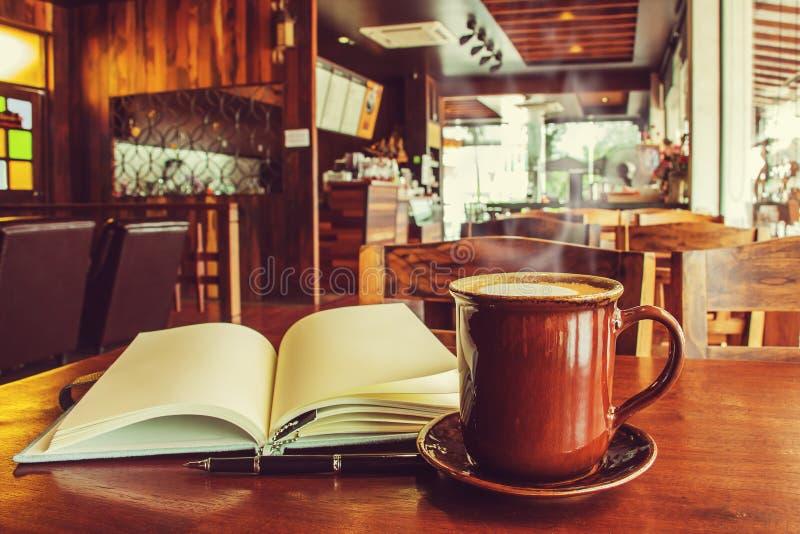 tasse de café avec le carnet ouvert sur la table en café (Processus de vintage image libre de droits