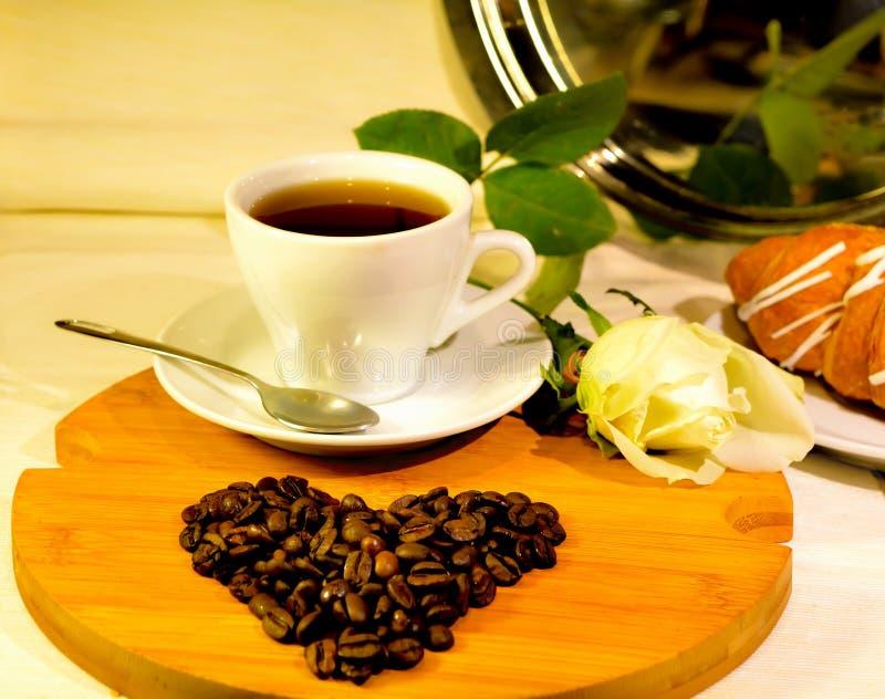 Tasse de café avec le coeur des grains de café et de la rose de blanc photographie stock libre de droits