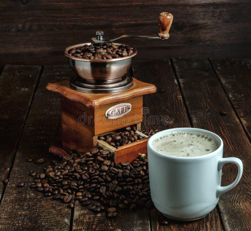 Tasse de café avec le moulin et haricots sur la table foncée image stock