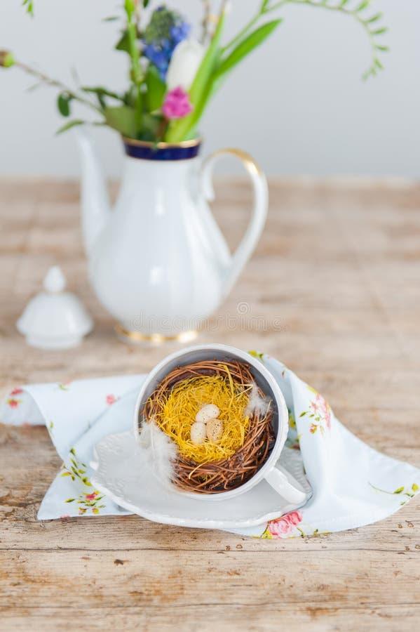 Tasse de café avec le nid de Pâques dans le premier plan Pot blanc de café de porcelaine avec des fleurs à l'arrière-plan photo stock