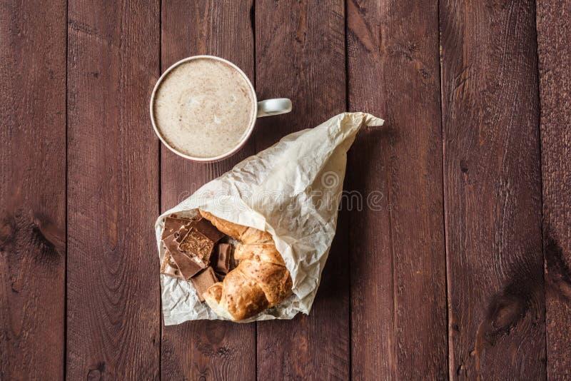 Tasse de café avec les barres fraîches de croissant et de chocolat pour le petit déjeuner photo stock